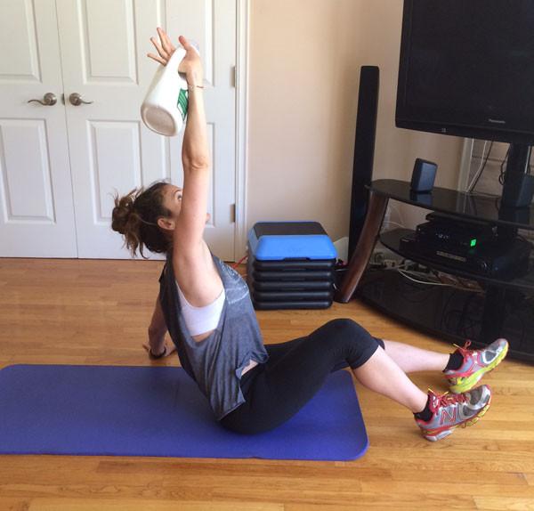 Mulher de camiseta, leggin e tênis, esta sentada em cima de um tapete de yoga azul, uma mão está apoiada no chão e a outra para cima levantando um galão de amaciante, utilizado para substituir um kettlebell