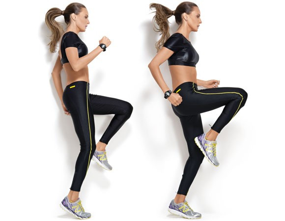 Uma mulher de top, calça preta e tênis, está fazendo o movimento de corrida no lugar, que é elevar os joelhos até a altura do quadril, alternando bem rápido as pernas e braços sem sair do lugar.