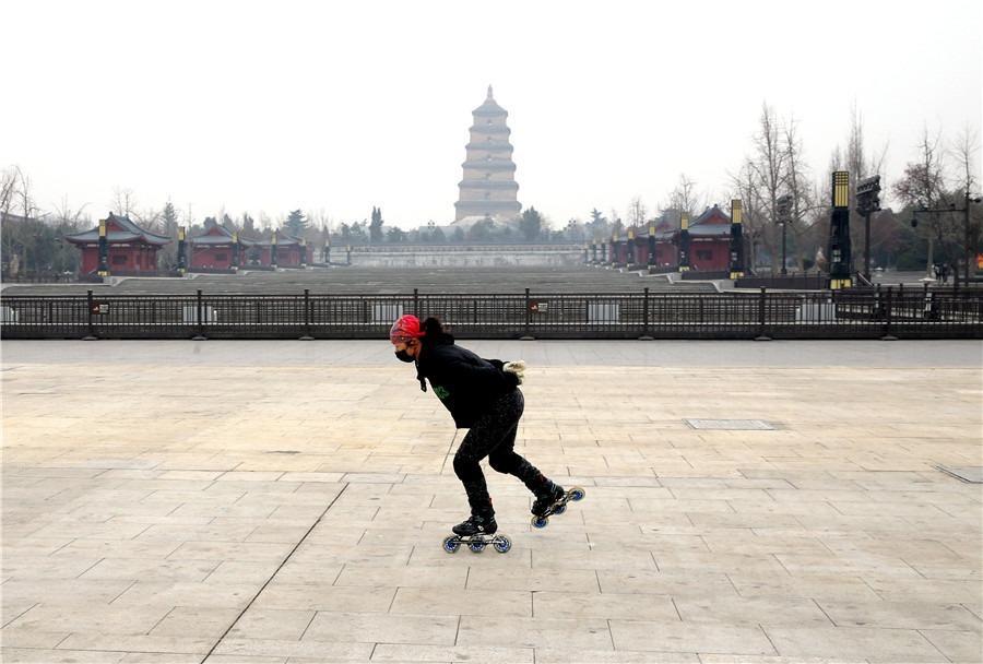 um patinador de velocidade, patinando em um espaço público vazio e ele está de máscara