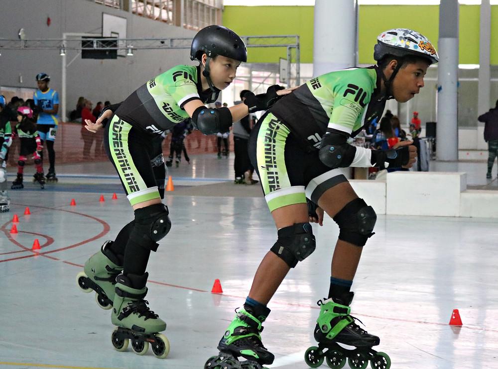 doi meninos patinando juntos em uma prova por equipe