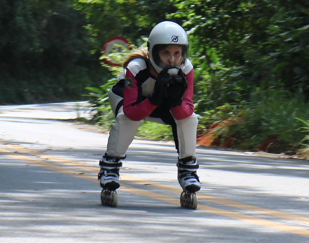 Foto da atleta Camila Cavalheiro descendo uma ladeira, na posição agachada, cotovelos a frente dos joelhos e mãos juntas. Saindo de uma curva em alta velocidade.