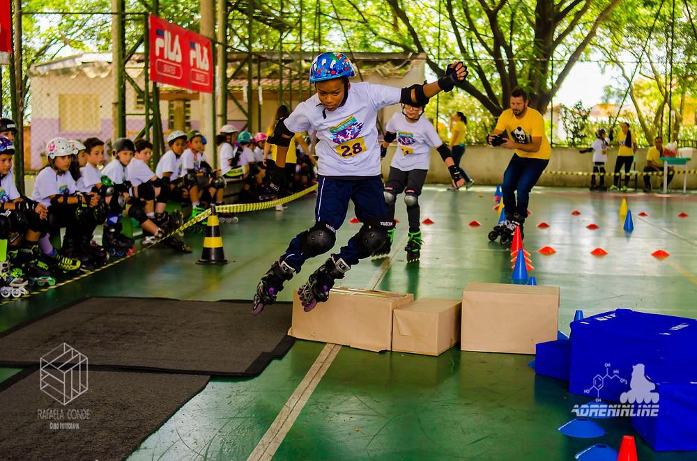 menino em uma corrida de skate cross pulando caixas em uma quadra poliesportiva,