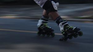 Foto de um patinador, com foco no patins, em alta velocidade, executando o freio de calcanhar