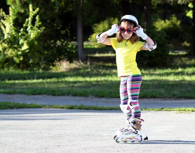 menina parada com uma camiseta amarela e calça colorida, de patins e equipamentos de proteção com óculos escuro no rosto e segurando no óculos