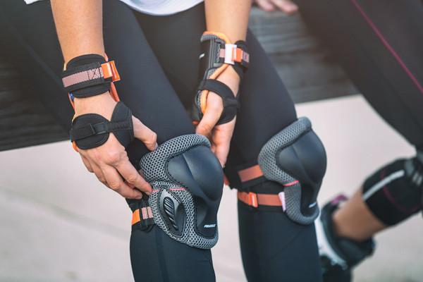 Mulher sentada de calça preta, ajustando sua joelheira da powerlide com tirar e velcro laranja, em suas mãos estão as munhequeiras da mesma marca e tiras de velcro também na cor laranja e preto.