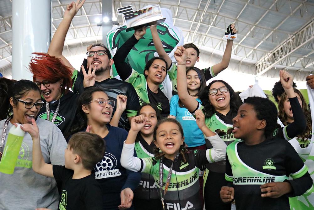 """Fotos de atletas pulando e gritando """"Tricampeão"""" e nossa treinadra com troféu na mão em cima do pódio."""