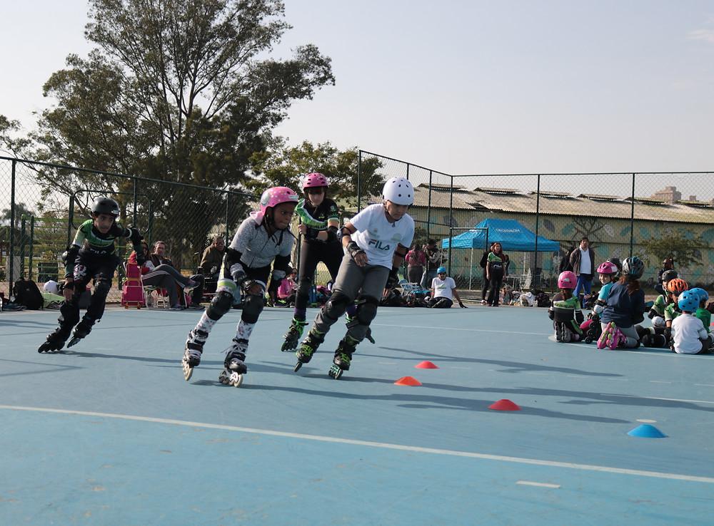 crianças fazendo a curva em uma corrida de patins, algumas crianças sentadas no meio da quadra e pais e responsáveis sentados na lateral da qudra. Quadra de cor azul da decathlon.