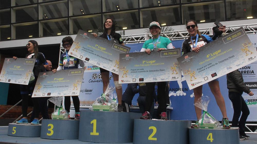 imagem do pódio feminino, com cada atleta segurando um cheque