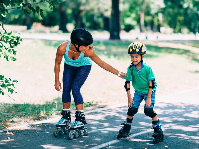 Mãe com patins abaixada segurando no braço do filho que está de patins e equipamentos de proteção aprendendo a patinar, de fundo uma pista e árvores como se estivessem em um parque.