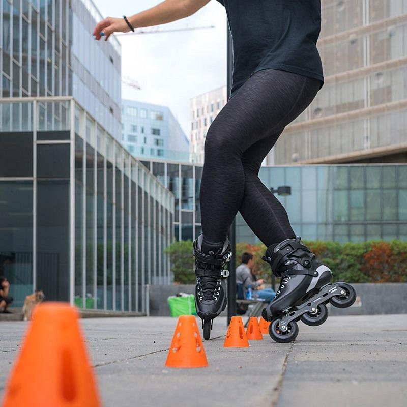 Pernas de mulher de leggin preta, fazendo manobras entre os cones de laranjas de slalom freestyle, aofundo algunes prédioss