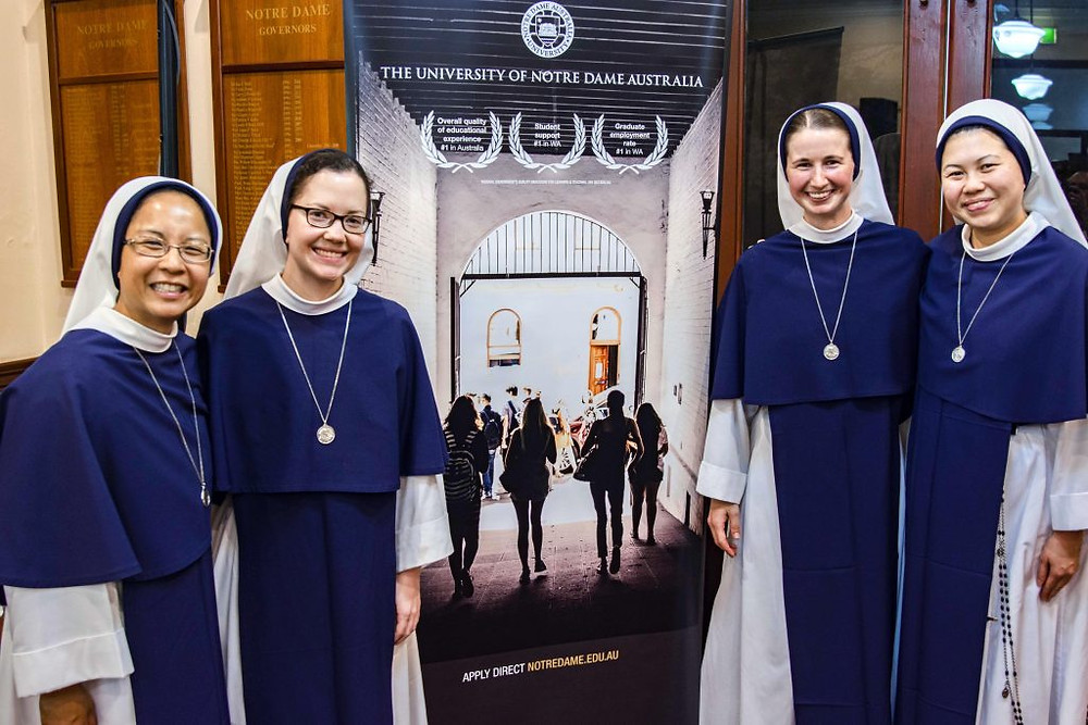 Four Sisters of Lilfe standing on by a banner.