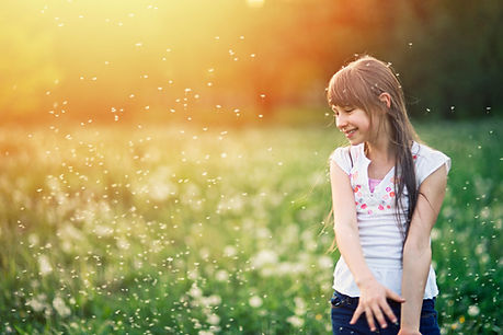 A young white girl with long brown hair smiling in a field filled with pollen and flowers.