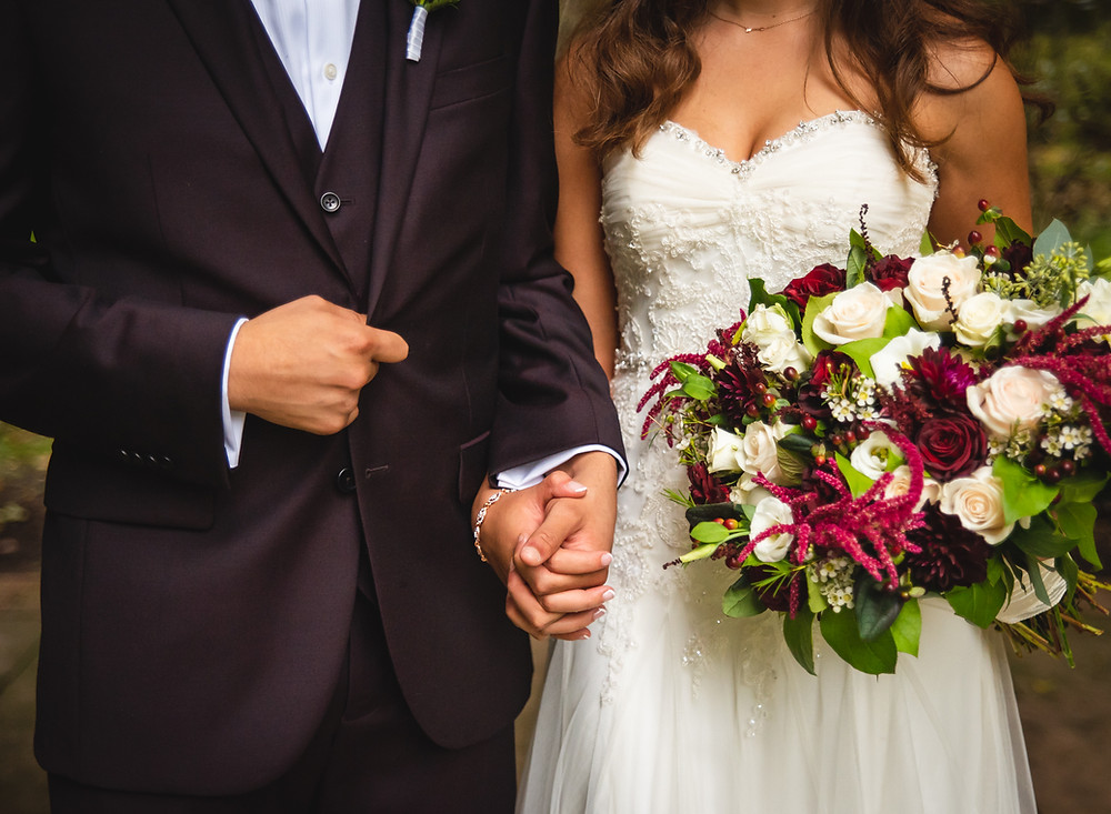 Bride and groom holding hands with wedding bouquet