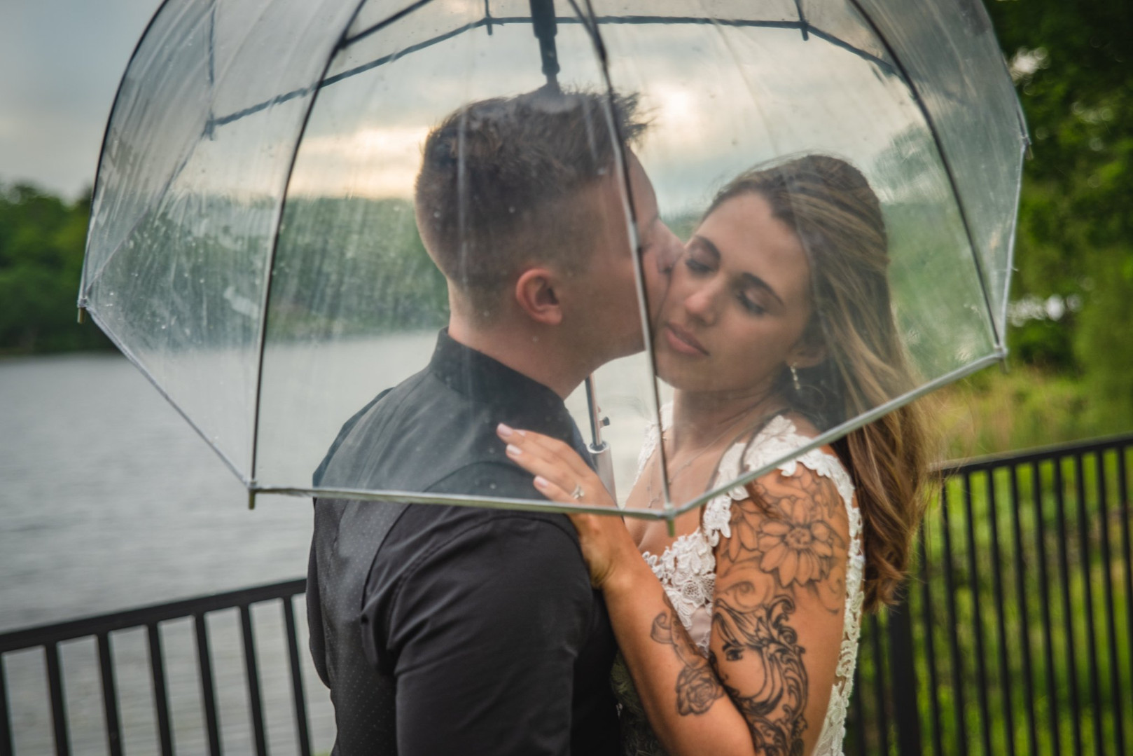bride and groom kissing under an umbrella in the rain - CT wedding photos