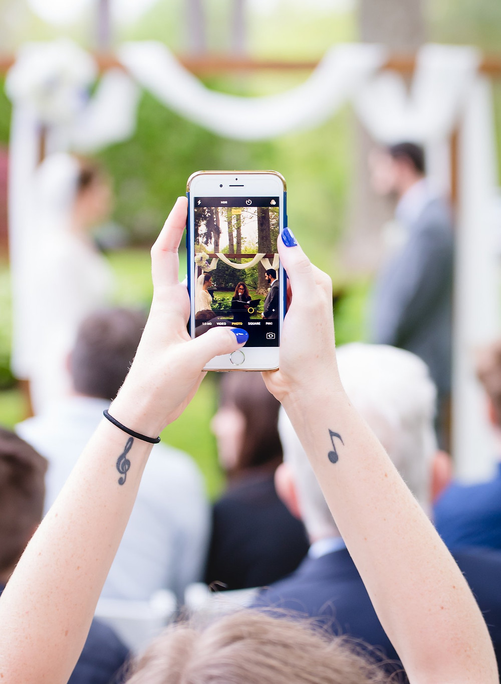Woman holding a cellphone to take a photo during a wedding ceremony - CT Wedding Photographer
