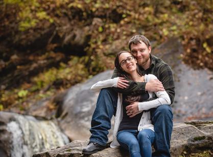 couple hugging in front of a waterfall for their engagement photo
