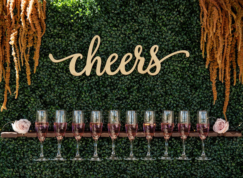 "leafy champagne wall with wooden ""cheers"" cutout"