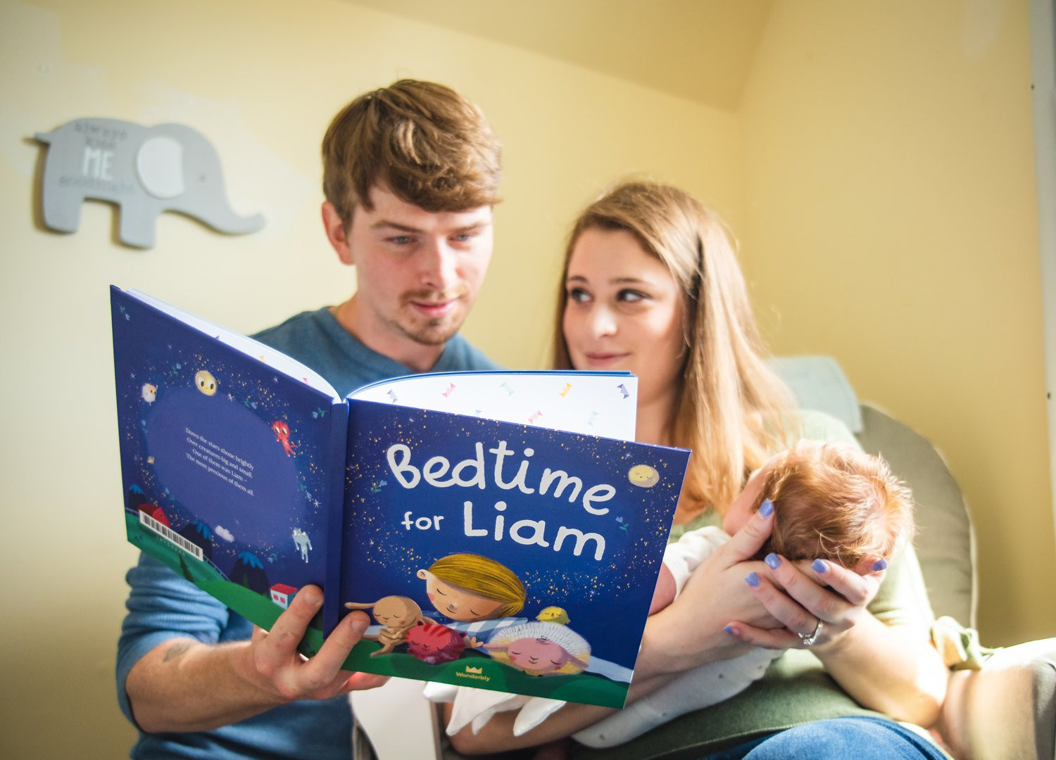 new parents reading their newborn baby a story