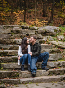 couple sitting on stone stairs and smiling at Kent Falls CT