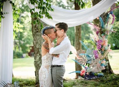 wedding couple kissing during backyard wedding ceremony