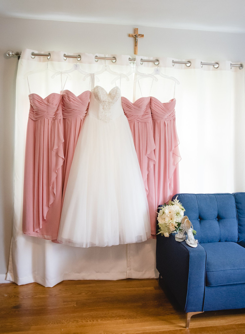 bride and bridesmaid's dresses hanging in a window