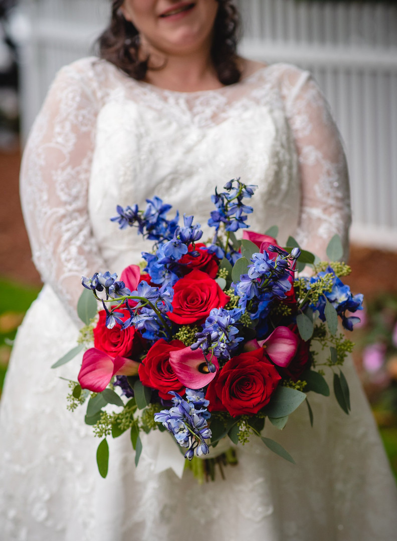 bride holding a blue and red floral bouquet