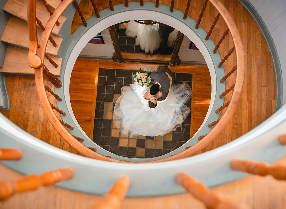 wedding couple kissing underneath spiral staircase at New England bed and breakfast