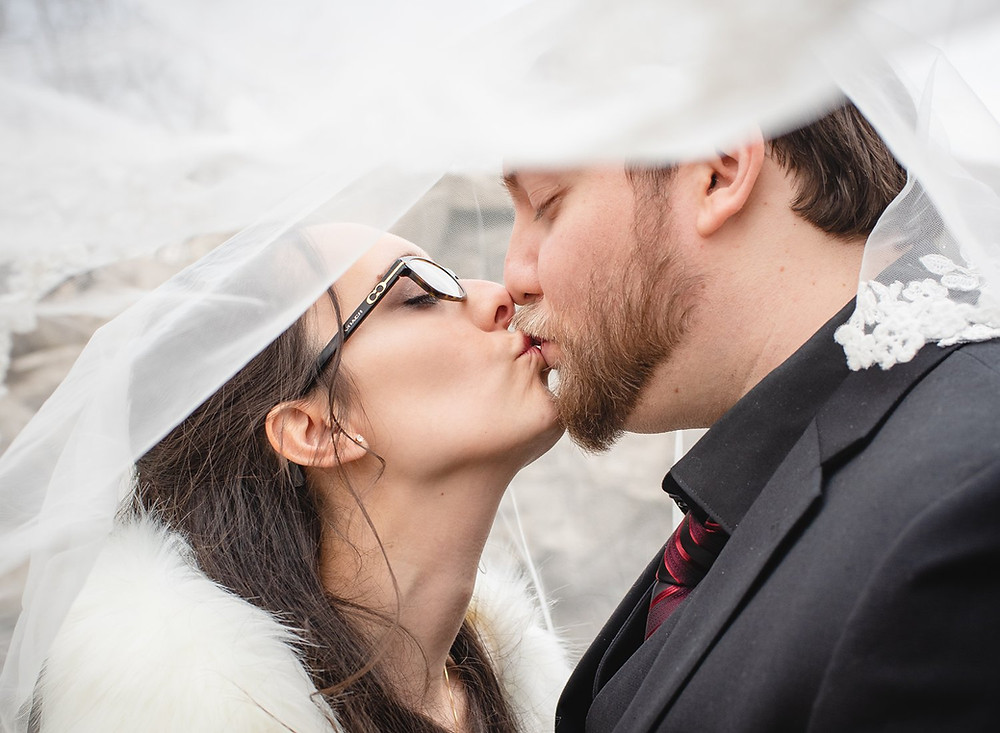 Cute couple kissing under the bride's veil at their wedding at Aria in Prospect CT