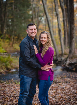 couple posing and hugging in front of a stream in the woods