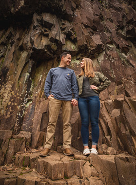 couple standing on rocky cliff face for their engagement photo