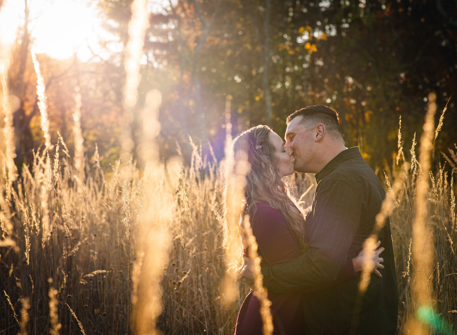 golden-hour portrait of a couple kissing in a tall grass meadow