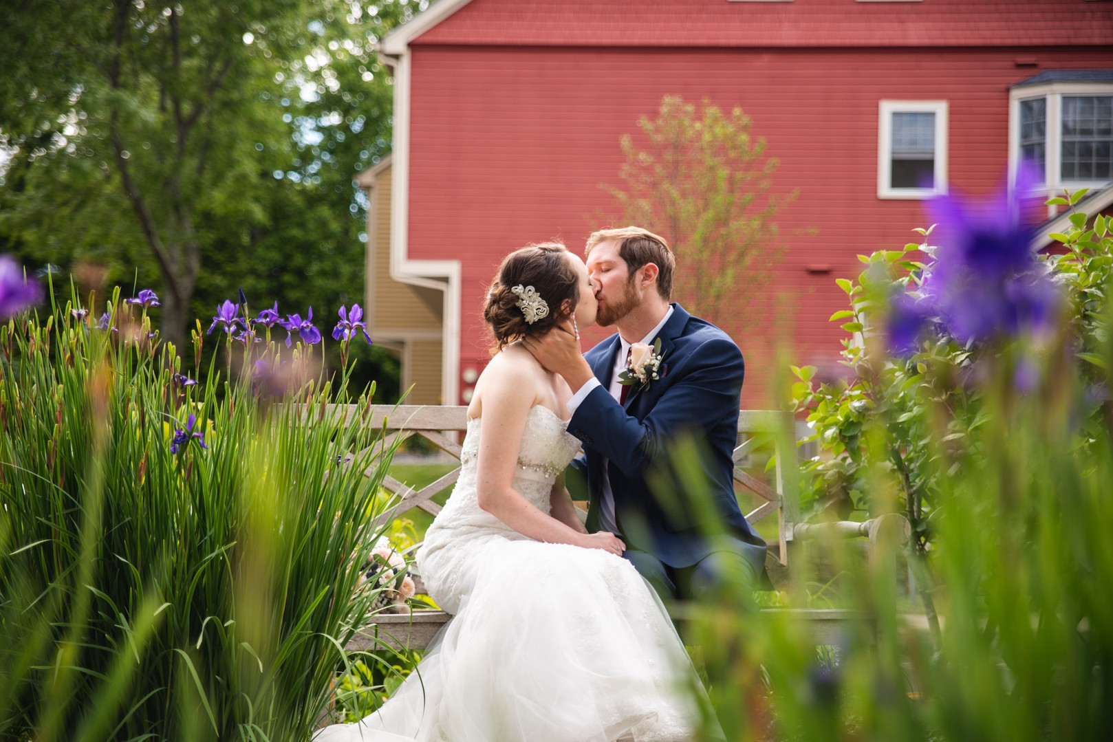 bride and groom kissing on bench in garden at Saybrook Point Inn & Marina CT