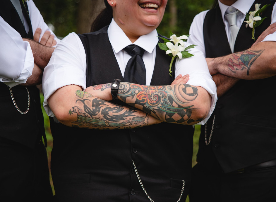Offbeat lesbian bride shows off tattoos with her wedding party