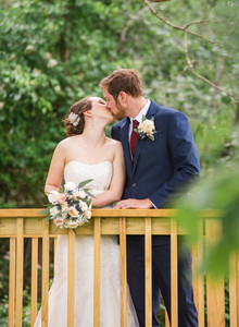 Bride and groom kissing on a boardwalk at Saybrook Point Inn