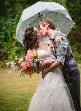 bride and groom kissing under an umbrella