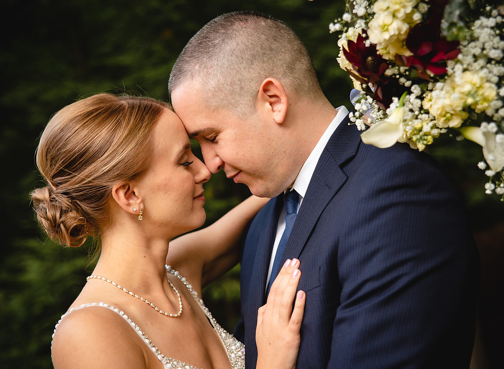 elegant couple touching noses. wearing wedding clothes and holding bouquet of flowers