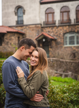 couple hugging in front of Heublein Tower for their engagement photos in CT