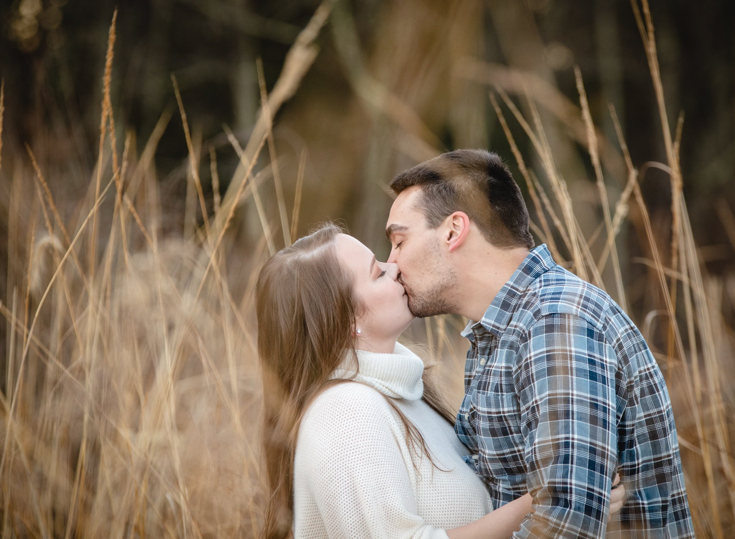 couple kissing in a grassy meadow at Valley Falls in Vernon CT for engagement photos