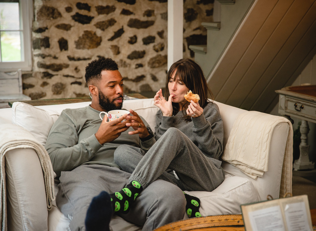 engagement lifestyle photo of couple sharing donut and coffee