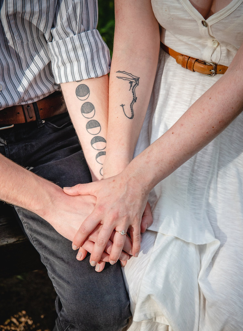 close up detail of a couple's unique tattoos on their arms