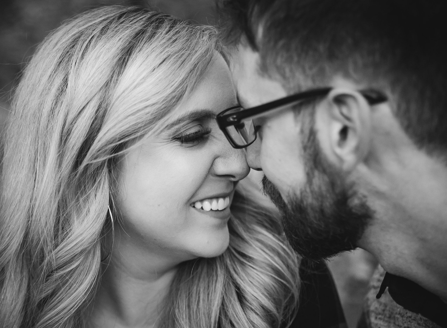 black and white engagement photo of a couple laughing