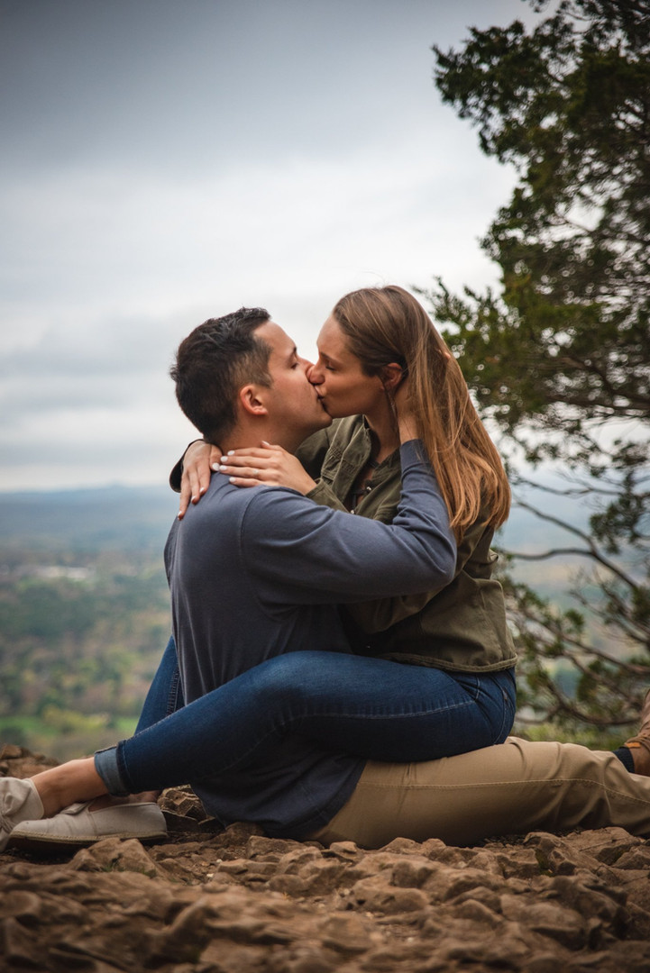 Couple kissing on top of mountain at Heublein Tower for engagement photos in CT