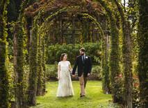 wedding couple walking through arches at Elizabeth Park in Connecticut
