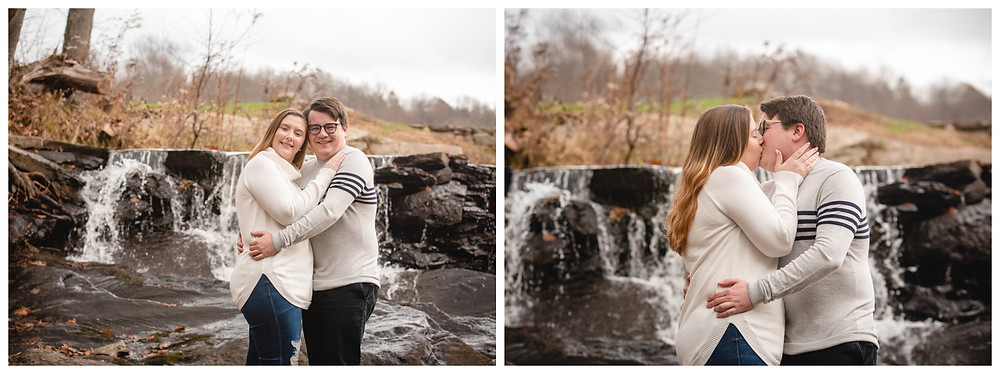 Couple posing and kissing in front of a waterfall for their engagement photography session at Valley Falls State Park in Vernon Connecticut. They are both wearing cream-colored sweaters.