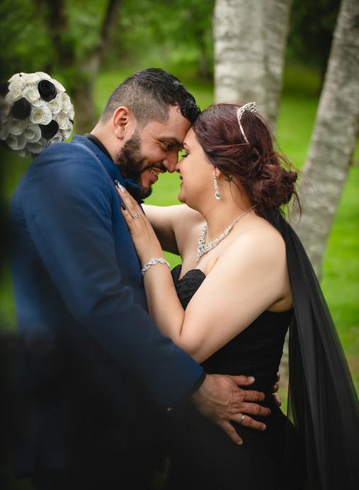 bride in black wedding dress with groom in blue suit