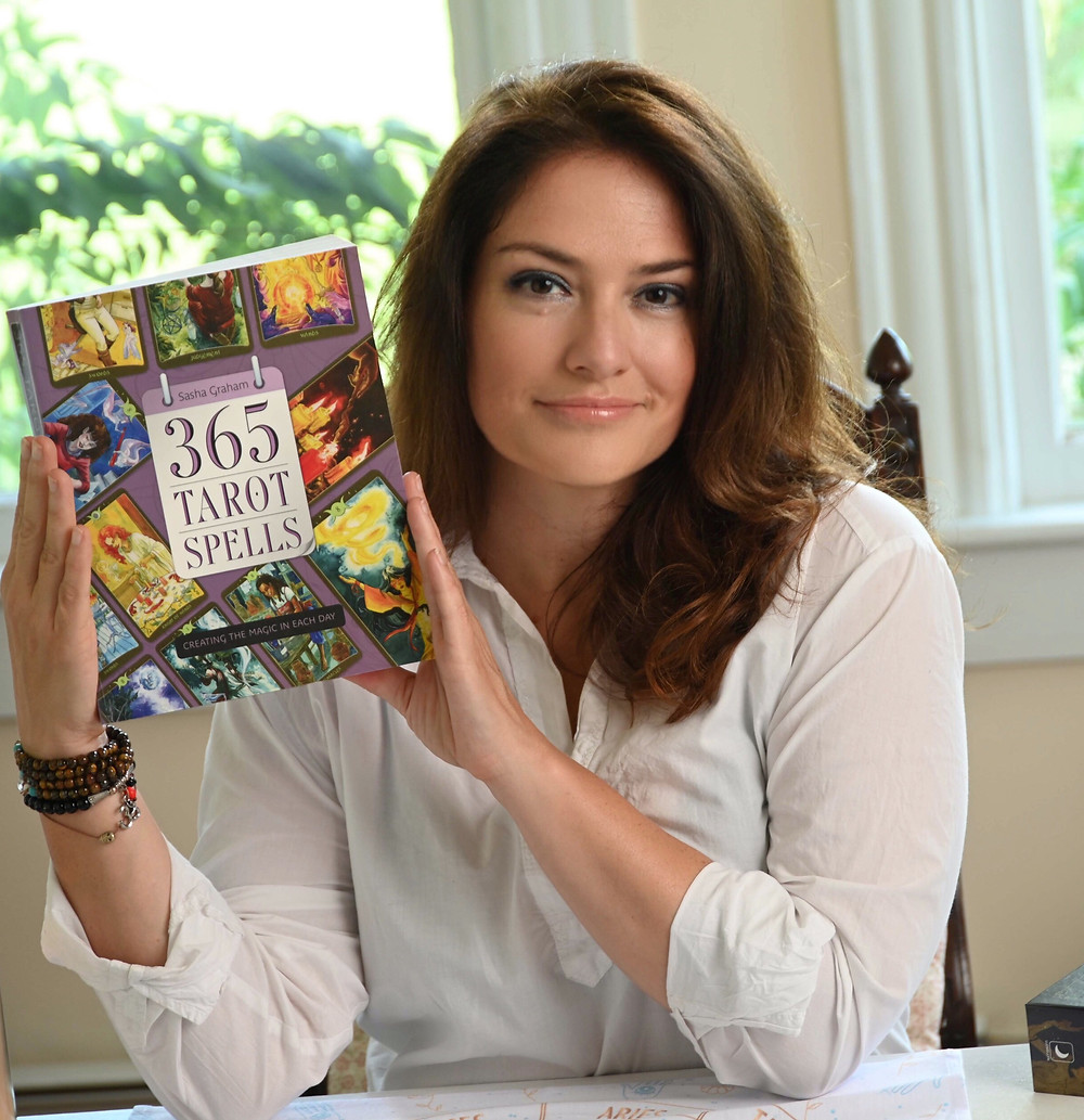 Author and Actress Sasha Graham holds 365 Tarot Spells, her Llewellyn book of tarot magic for every day of the year.