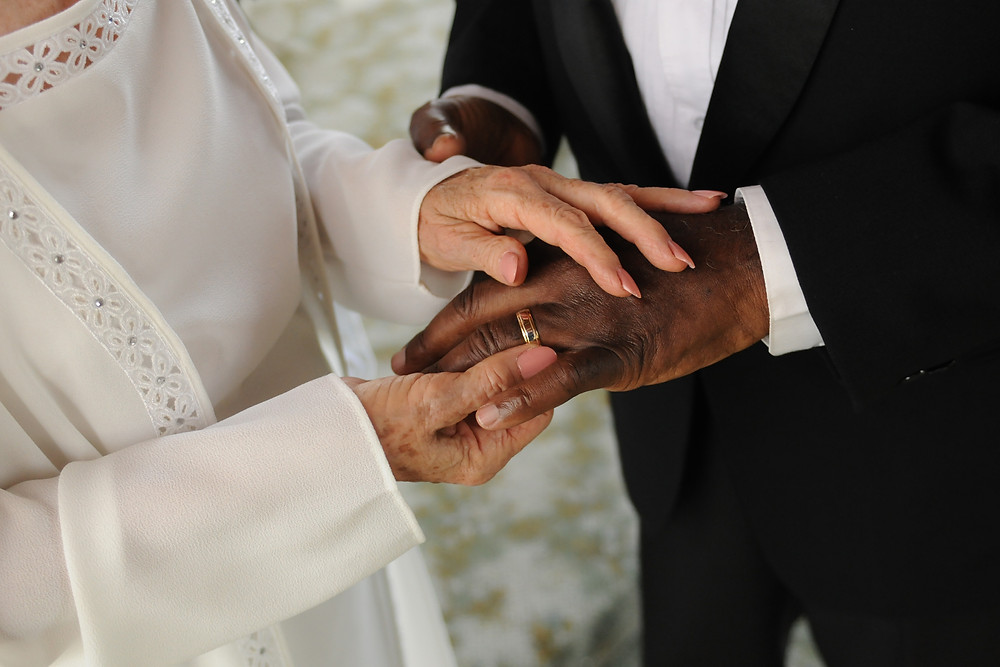 Elderly couple exchanging rings