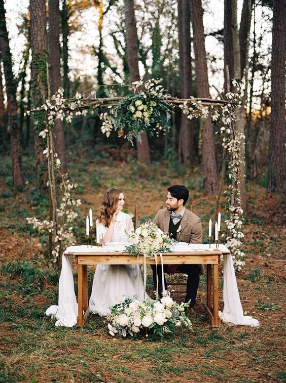 A couple sitting under an archway at a woodland wedding