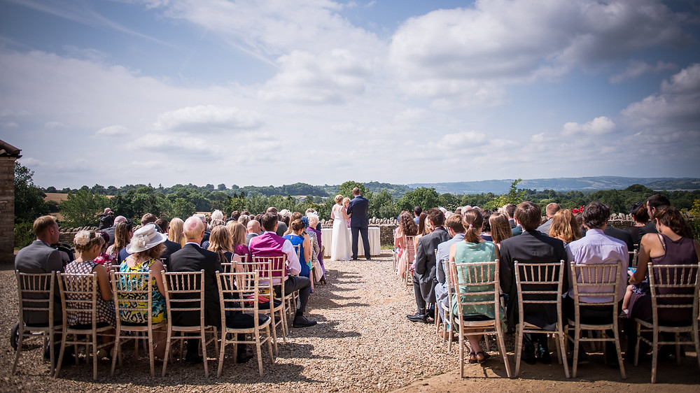 An outdoor wedding ceremony at Folly Farm in Somerset - photo credit Betty Bhandari