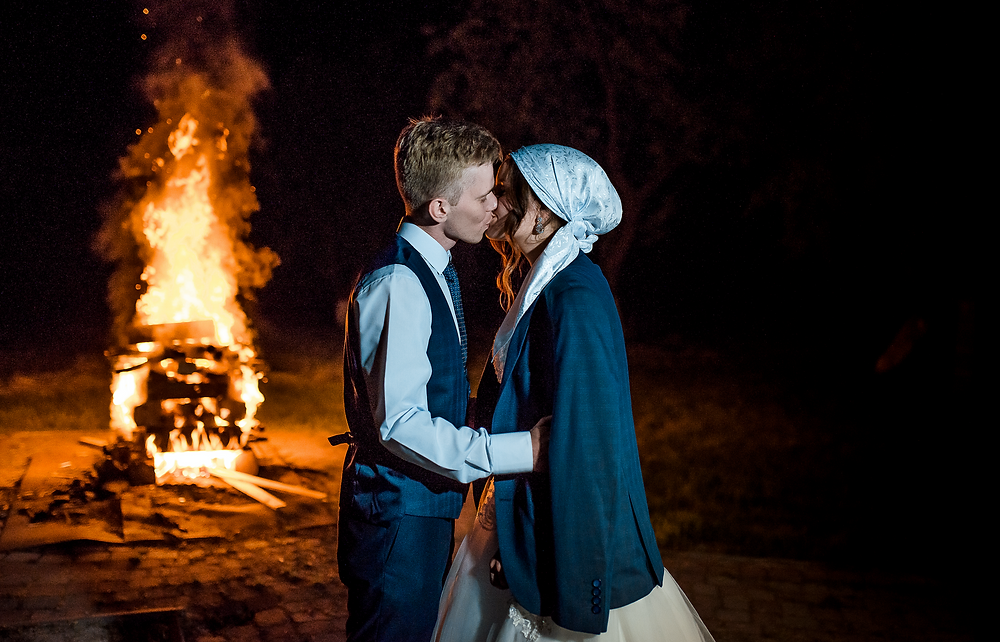 couple kissing in front of bonfire